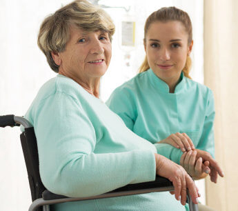 elderly woman in a wheelchair with her caregiver